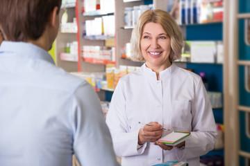 Ordinary guy talking to pharmacist at pharmacy