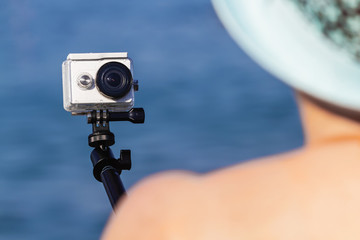 Young woman in the hat is taking selfie photo and video on action camera using selfie stick on the sea. Closeup, selective focus