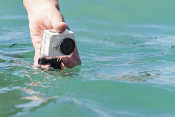 A man is taking photo and video above the water on action camera in underwater case. Closeup, selective focus