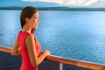 Wall Mural - Luxury travel cruise ship elegant Asian woman on Alaska destination cruising holiday. Happy lady looking at sunset view of ocean from boat balcony deck.