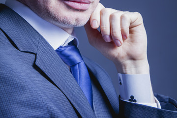 businessman with a ace card in a sleeve as symbol of cheating and dishonest games (Business, fraud, profit, crime, money laundering concept)