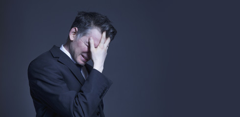 Frustrated and stressed businessman feeling depressed after fail (bankruptcy, debt, poverty and stress concept)
