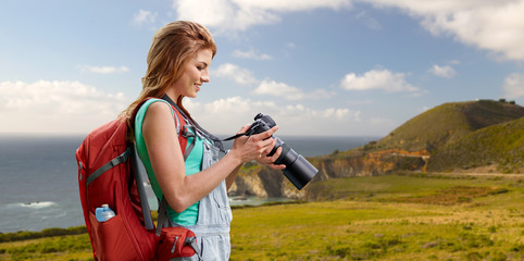 travel, tourism and photography concept - happy young woman with backpack and camera photographing over big sur coast of california background
