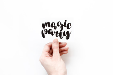 Minimal composition on a white background with girl's hand holding card with quote - Magic party