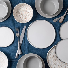 Empty ceramic tableware. Ceramic plates on jeans tablecloth or runner. Overview empty food table with tableware. Set of different modern white plates and bowls.Top view or flat lay.Copy space for text