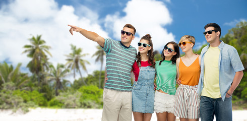 friendship, travel, tourism and summer holidays concept - group of happy smiling friends in sunglasses hugging and pointing finger to something over tropical beach background in french polynesia