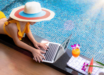 Hand of woman playing on the keyboard of notebook computor at the edge of swimming pool, enjoy with orange juice and water melon fruit while relax in summer time vacation