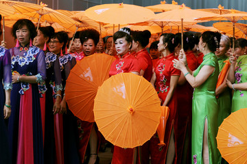 Performers wearing cheongsams wait to perform at a cultural industry expo in Kunming