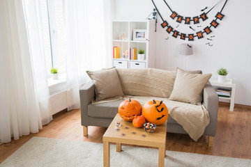 holidays, decoration and party concept - home room with jack-o-lantern or carved pumpkin, halloween decorations and treats on wooden table
