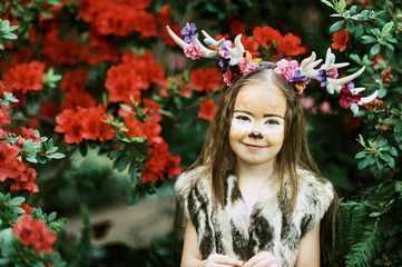 Fairy tale girl. Portrait a little girl in a deer dress with a painted face in the forest. Big antler. Fantasy girl. Springtime.