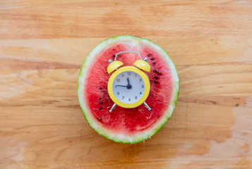 little alarm clock and cut watermelon on wooden table. Above view