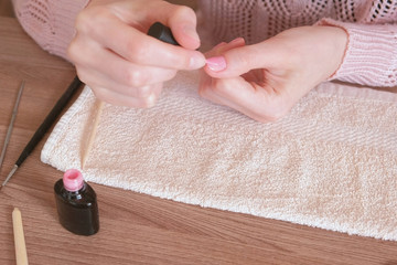 Woman puts first coat of pink shellac on her nails. Close-up hands.