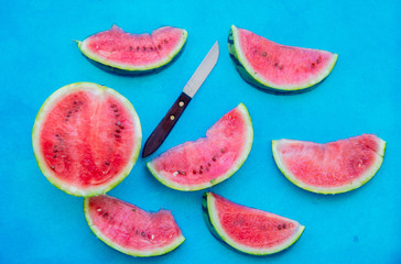 Watermelon and knife on blue background. Above view
