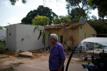 An Israeli man stands next to the scene where a rocket exploded in the southern Kibbutz of Yad Mordechai, Israel