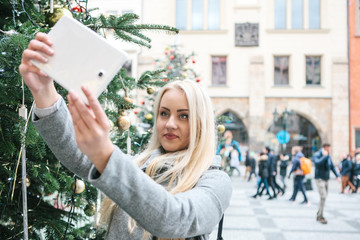 A beautiful young blonde woman or girl doing selfie or photographing next to a Christmas tree during Christmas holidays at the Old Town Square in Prague, Czech Republic.