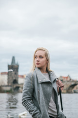 Fashionable blonde with long hair in a coat near Charles Bridge in Prague. Beautiful young woman outdoors.