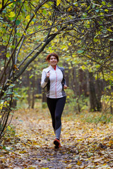 Photo of young girl running through autumn park