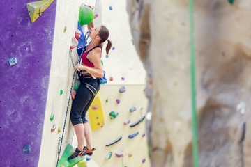Photo of young woman with safety rope practicing on climbing wall in gym.