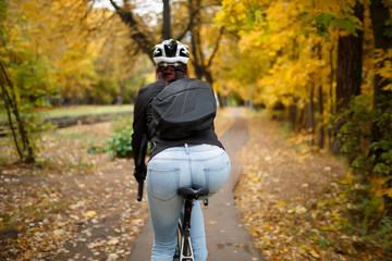 Rear view of woman wearing helmet on bicycle