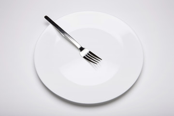 white empty dish with fork on the white background.