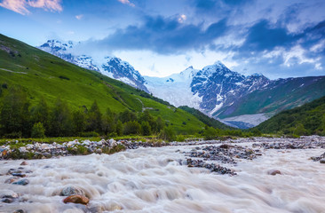 From the river shore opens view on fantastic glacier. The landscape with the great beautiful mountains in the sun rays. Eco tourism. Spring scenery. Upper Svaneti, Georgia, Europe.