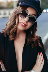 Closeup portrait of young beautiful fashionable woman with sunglasses. Lady posing on dark grey background. Model wearing stylish cap hat, jacket. Girl looking at camera. Female fashion.Toned