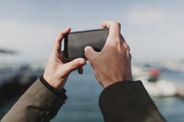 Close up of man hands holding a mobile phone to take a picture during vacation.
