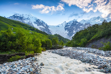 Beautiful mountain stream with colorful stones. The landscape with the great beautiful mountains in the sun rays. Eco tourism. Spring scenery. Upper Svaneti, Georgia, Europe.