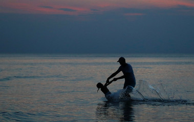 Man with a girl play in the sea after sunset at the Polish Baltic Sea coast near Choczewo