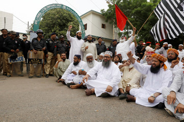 Police officers stand guard the entrance of the Provincial Election Commissioner office, as leaders and supporters of opposition political parties sit in protest against, what they say is alleged vote-rigging during the general election, in Karachi