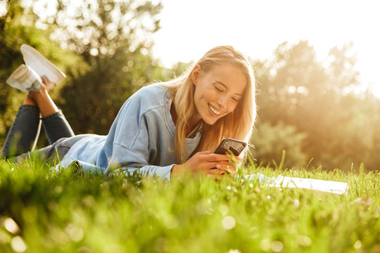 Portrait of a cute young girl laying on a grass at the park