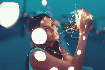 Sensual young woman playing with fairy lights outdoors looking into camera