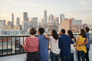 Rear View Of Friends Gathered On Rooftop Terrace Looking Out Over City Skyline
