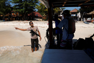 A policeman talks to visitors as he guards an empty island after foreign and domestic tourists fled after Sunday's earthquake in Gili Trawangan Island