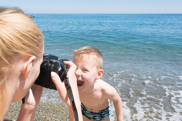 A woman is taking pictures of a boy on the beach. The mother takes a picture of her young son on vacation.