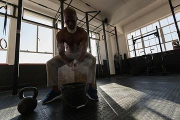 Senior man rubbing white powder on his hand before workout