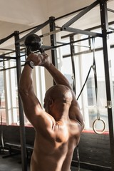 Senior man exercising with kettle bell in the fitness studio