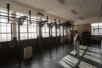 Senior man drinking water in the fitness studio