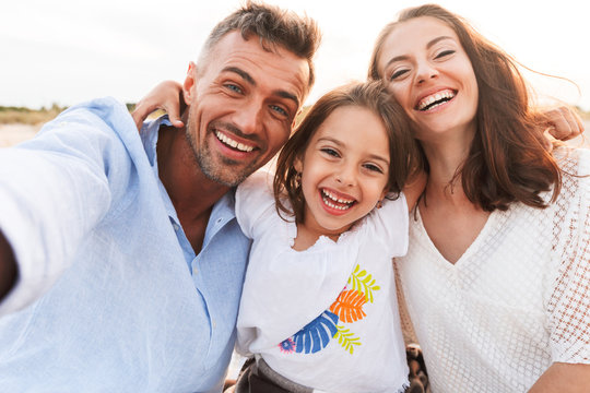 Family outdoors at the beach take a selfie by camera.