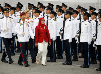 Singapore's President Halimah Yacob inspects the guard of honour at the National Day parade along Marina Bay in Singapore