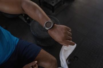 Smart watch on mans wrist in fitness studio