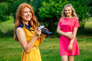 photosession beautiful young ginger redhead irish girl in a yellow dress and european blonde woman in pink dress photographed each other in the summer park. photoshoot of two model girlfriends