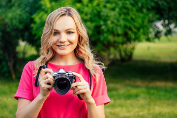portrait of photosession professional beautiful young blonde woman in a pink dress photographed in the summer park. photographer in photoshoot with a big camera and a cool lens