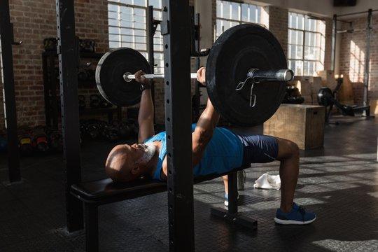 Senior man lifting barbell in gym