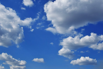 Blue cloudy sky with many white and grey clouds in summer day as background.