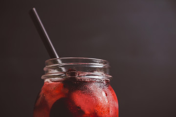 Cherry cocktail with ice in glass jar. Selective focus.