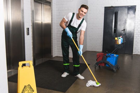 handsome young janitor mopping floor and smiling at camera