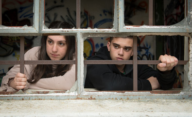 Two young teenagers, a boy and a girl, behind a broken window