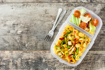 Lunch box with healthy food ready to eat.`Pasta salad on wooden table. Top view. Copyspace
