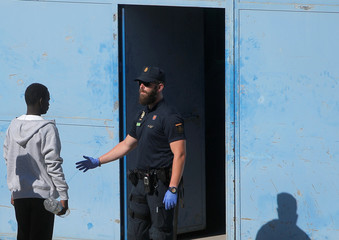 A migrant is led by a Spanish police officer into the new Center for Temporary Assistance to Foreigners after arriving at the port of Algeciras in San Roque